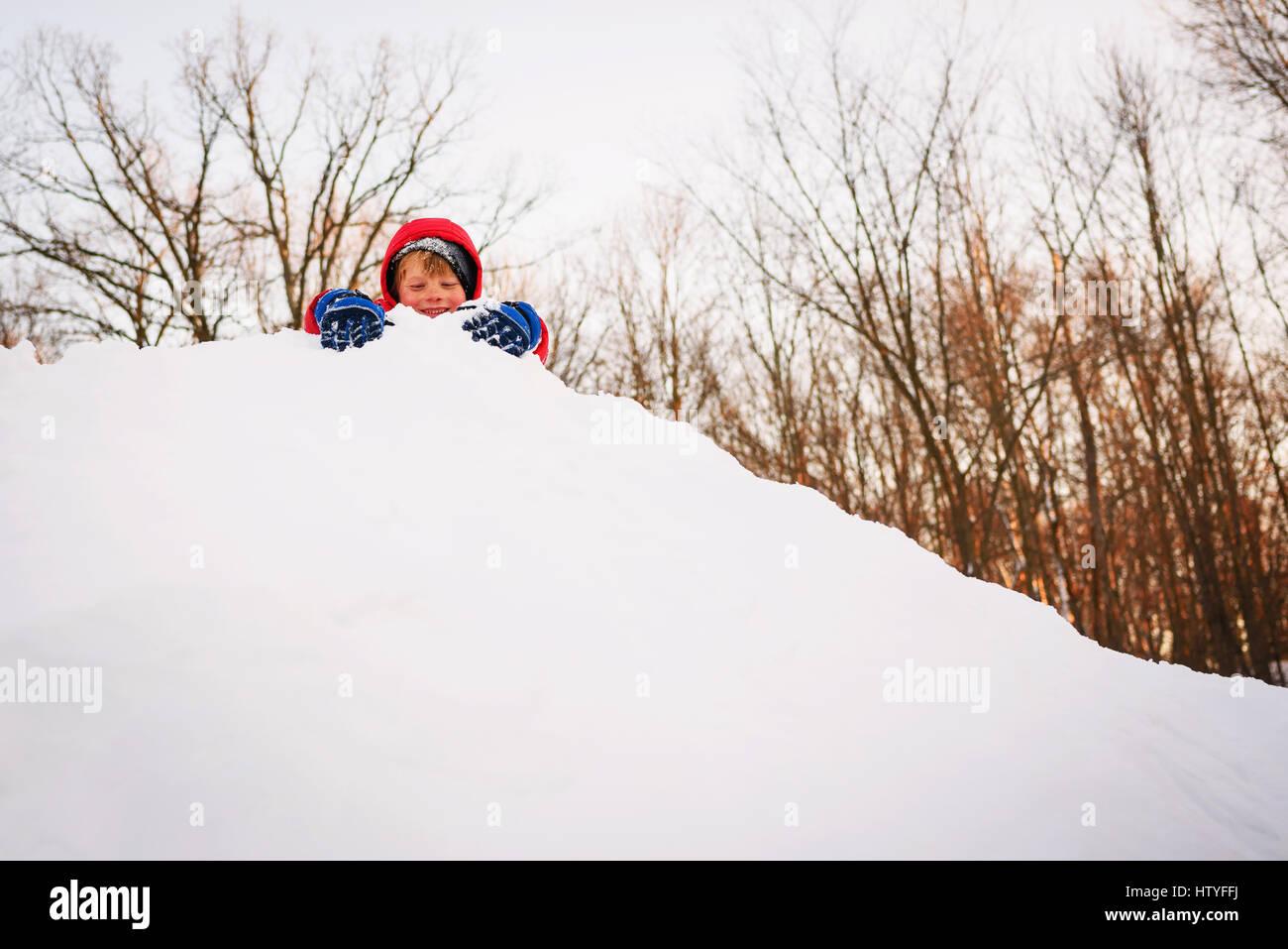 Niño jugando en la cima de un montón de nieve Foto de stock