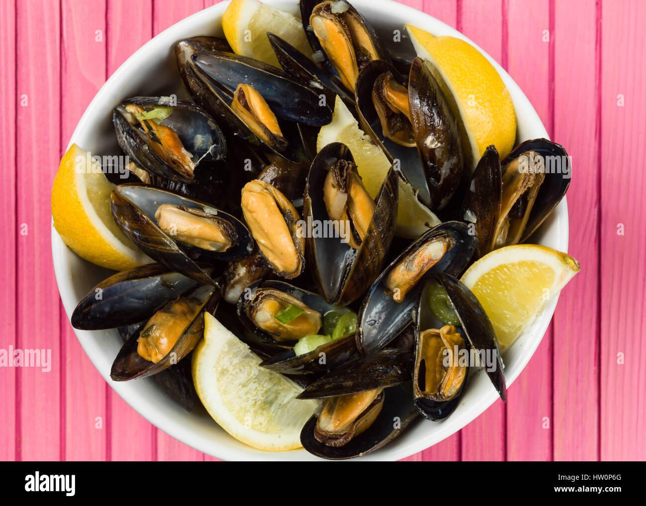 Cuerda de mejillones cultivados en una salsa de ajo y chalota con rodajas de limón Foto de stock