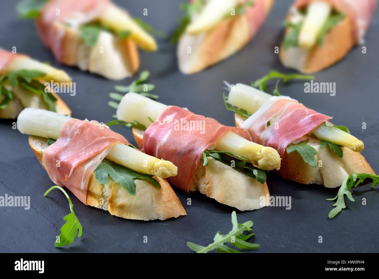 Deliciosos bocados con espárrago blanco sobre hojas de rúcula envueltos con prosciutto italiano Foto de stock