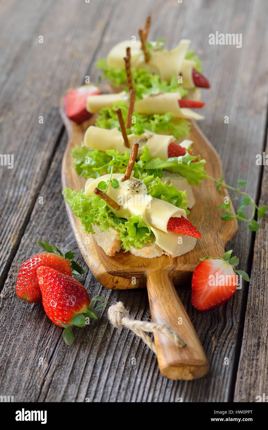 Canapés con deliciosos panes de queso y fresas en pan ciabatta italiana con hojas de lechuga Foto de stock
