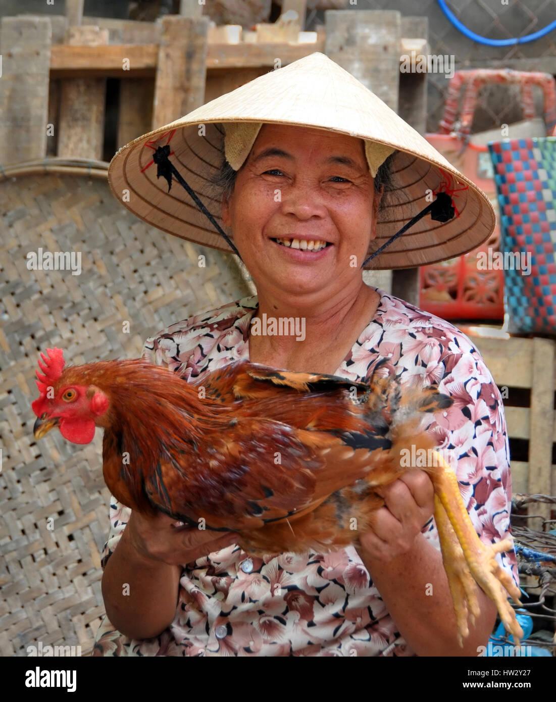 Una anciana proveedor ofrece un pollo vivo para la venta en los mercados de Hoi  An c4f169fd96d