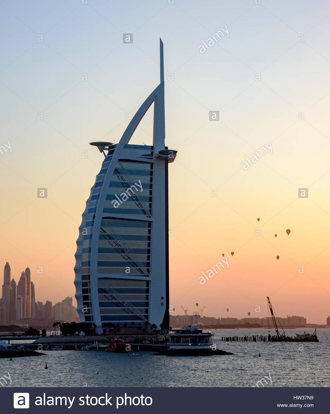 El Icónico Burj Al Arab Hotel con globos de aire caliente que pasa detrás de ella al atardecer tiempo, Dubai, EAU Foto de stock