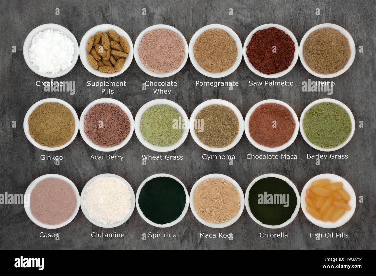 Salud body building polvos alimenticios y suplementos en cuencos de porcelana sobre fondo de mármol con títulos. Imagen De Stock
