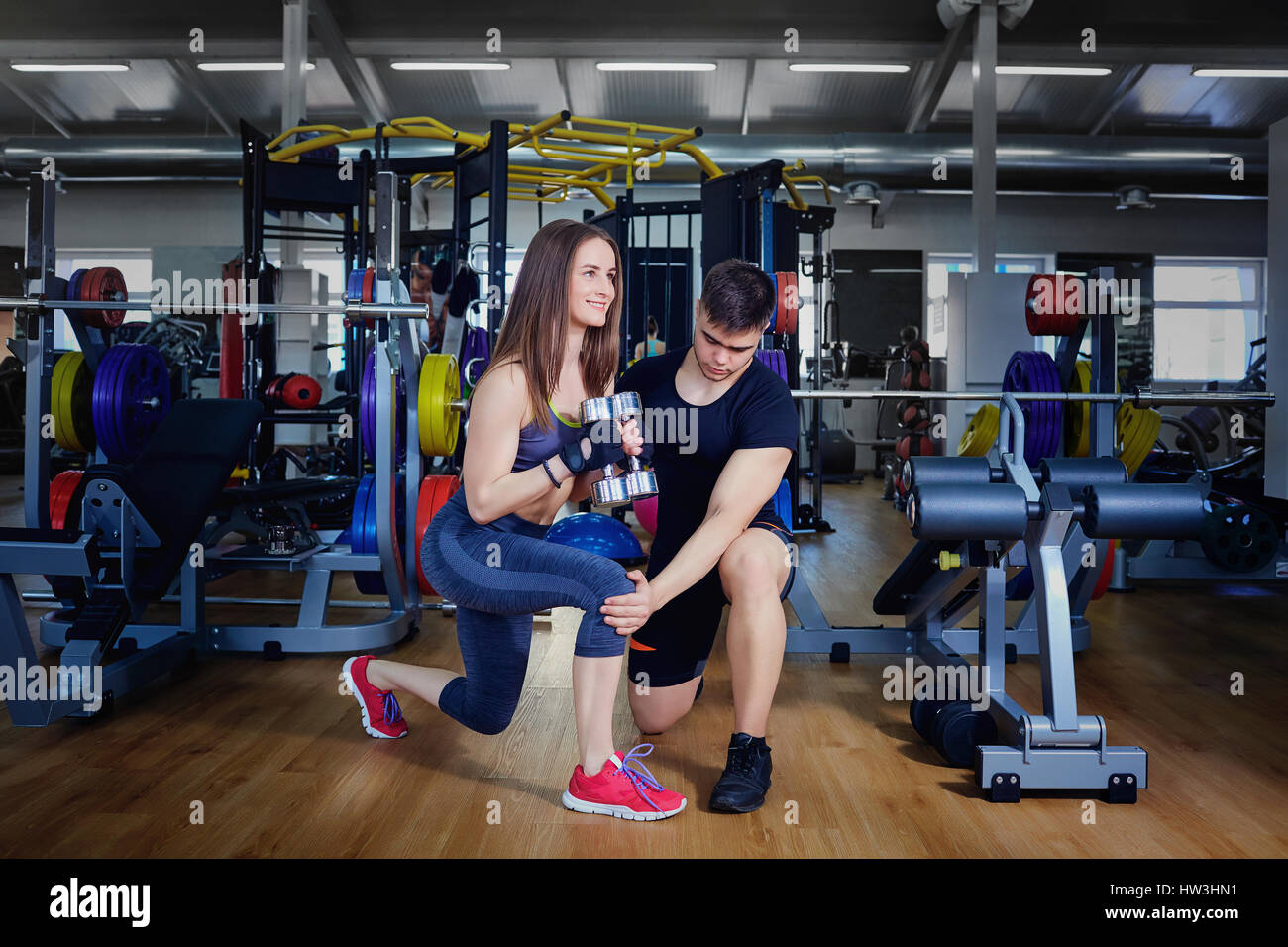 Entrenador personal instructor ayuda a hacer ejercicios para practicar deportes gi Imagen De Stock