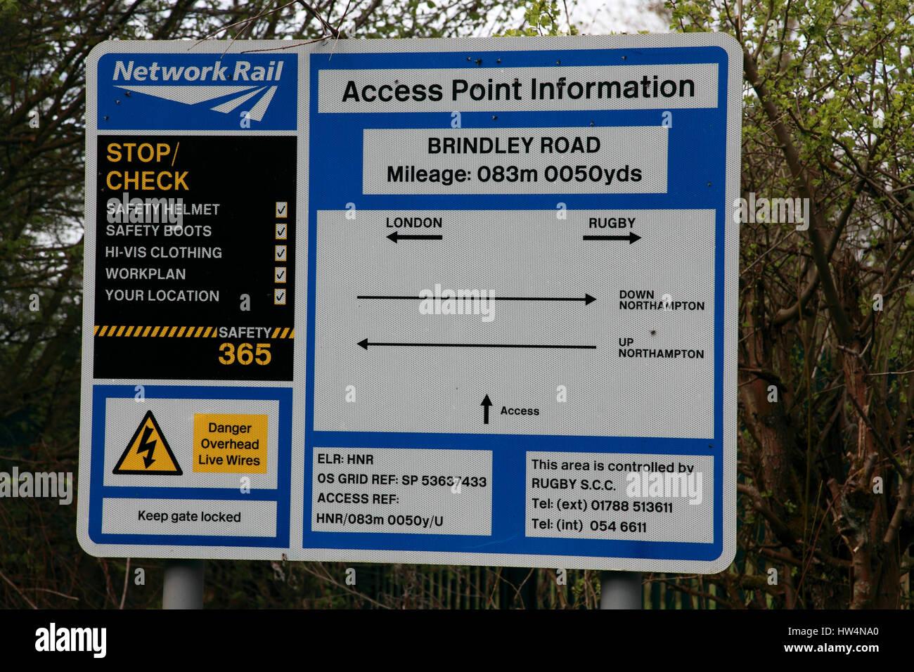 Una red de información del punto de acceso ferroviario firmar junto a un bajo puente llevando el ferrocarril Imagen De Stock