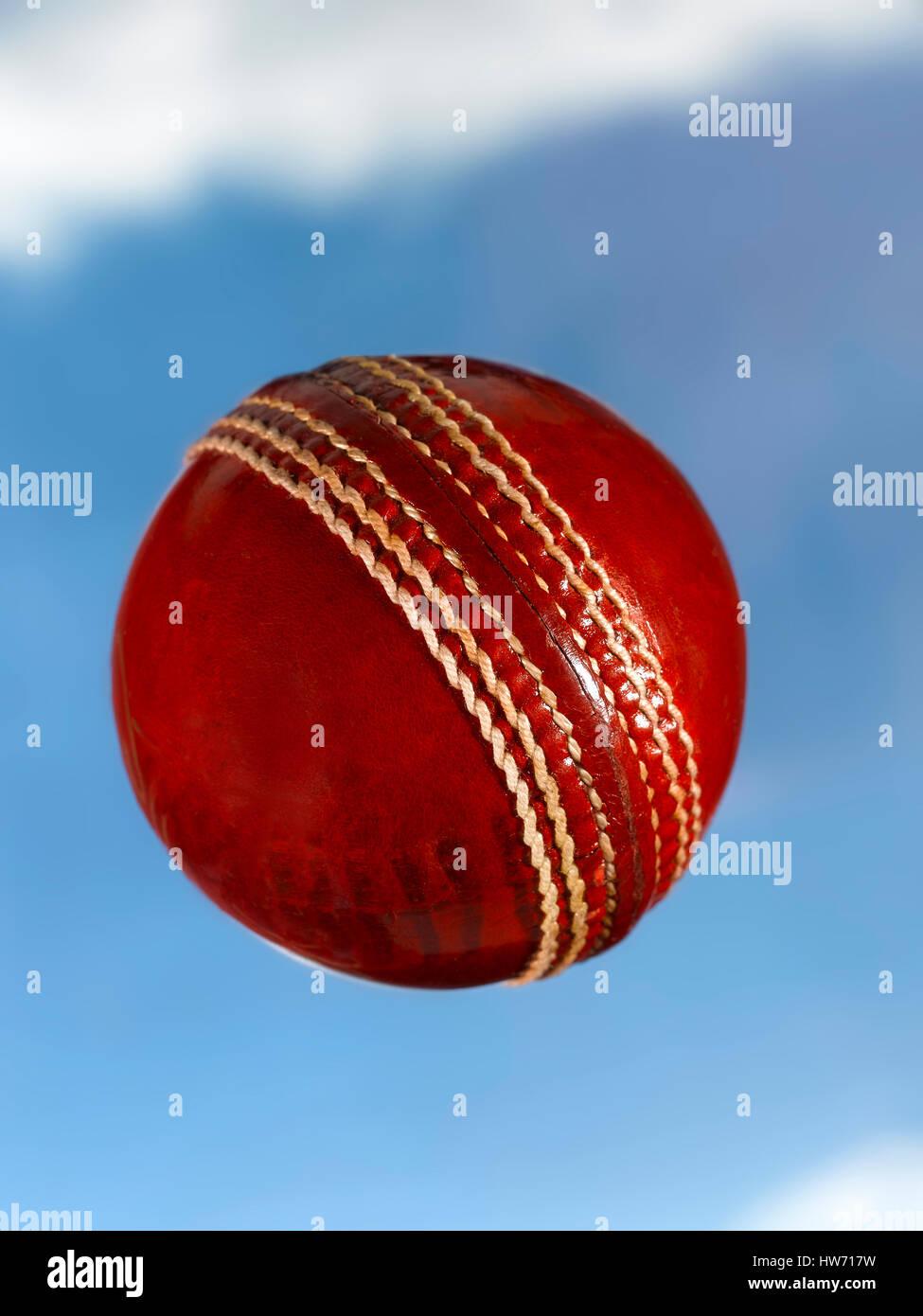 Bola de Cricket de cuero rojo volando a través del cielo Foto de stock