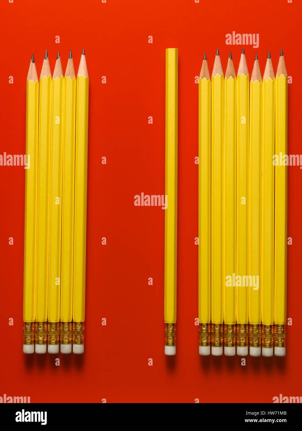 Lápiz amarillo aislado sobre un fondo rojo. Foto de stock