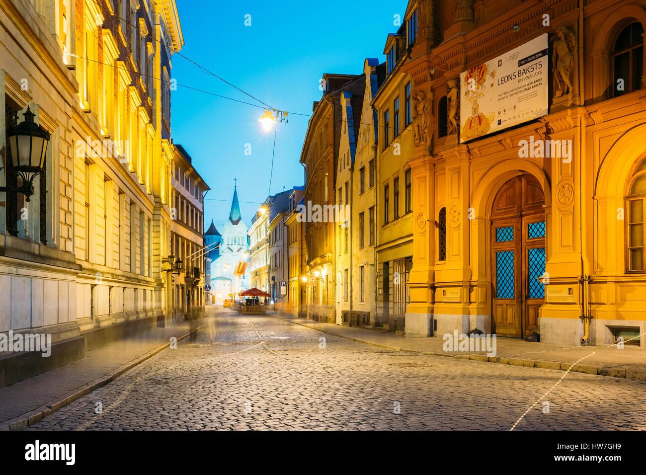 Riga, Letonia - Julio 1, 2016: Vista de Noche de la pils Street con la arquitectura antigua en un cálido amarillo Imagen De Stock