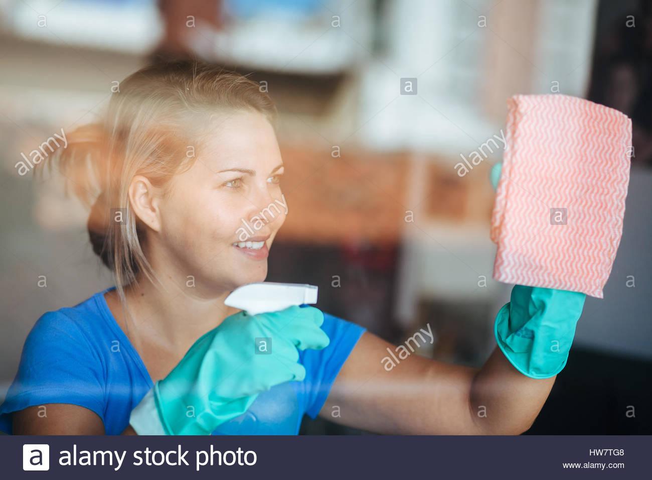 La gente, la casa y el concepto de limpieza - mujer feliz en guantes ventana de limpieza con un trapo y limpiador Imagen De Stock