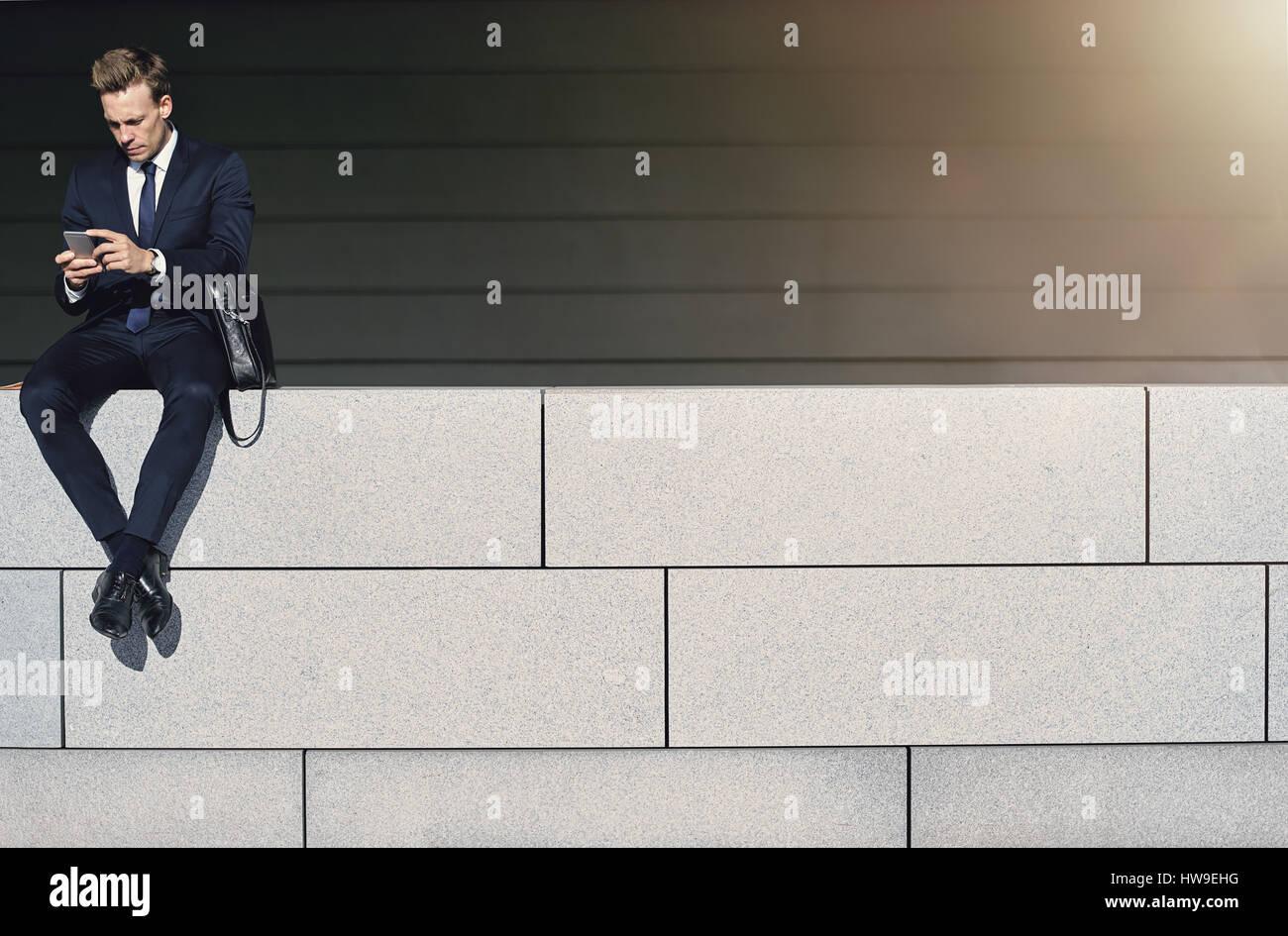 El empresario utiliza su smartphone mientras estaba sentado en la pared de ladrillo. Disparó al aire libre Imagen De Stock