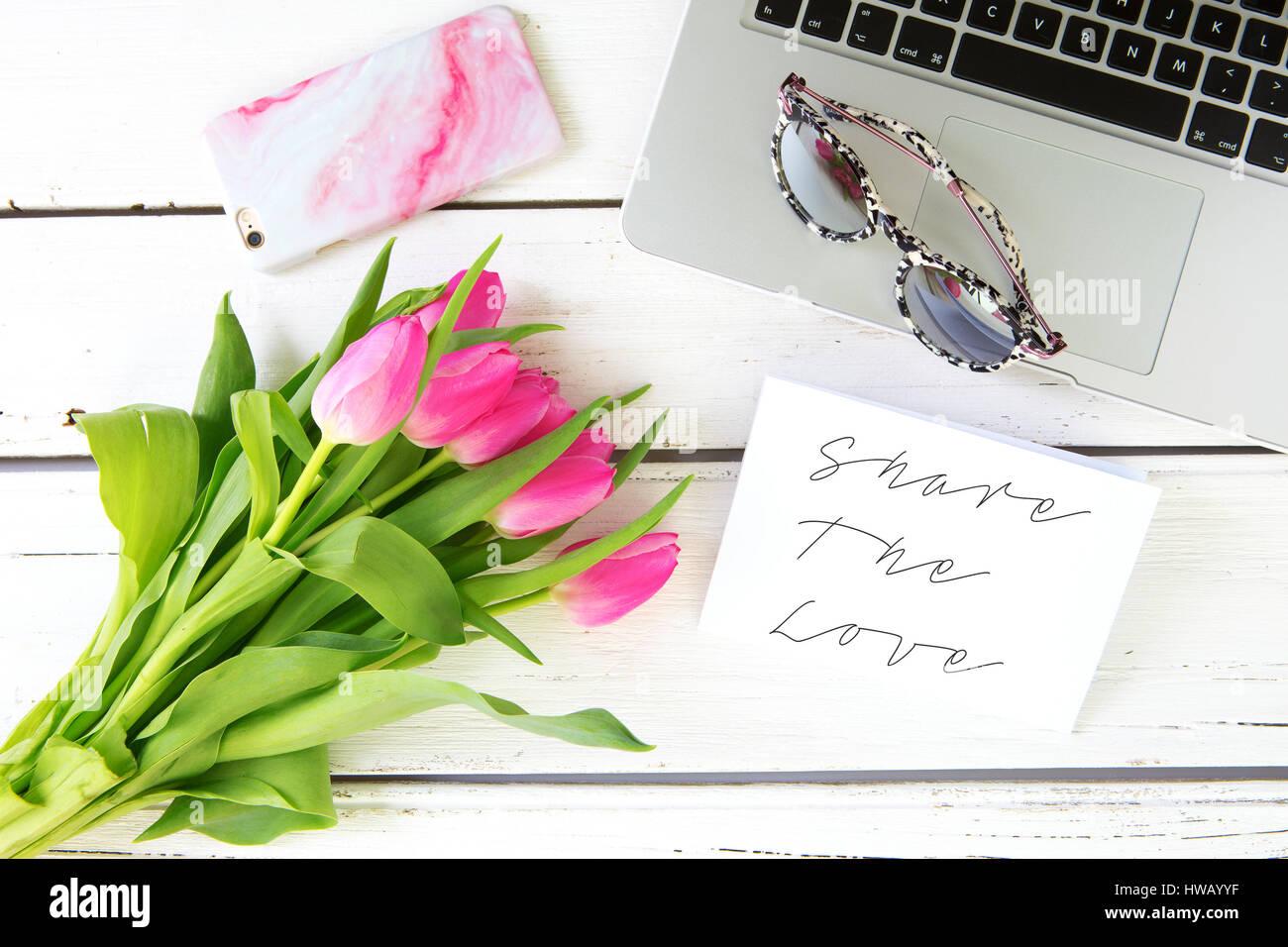 Compartir el mensaje de amor con tulipanes rosa sobre un fondo de madera blanca Imagen De Stock