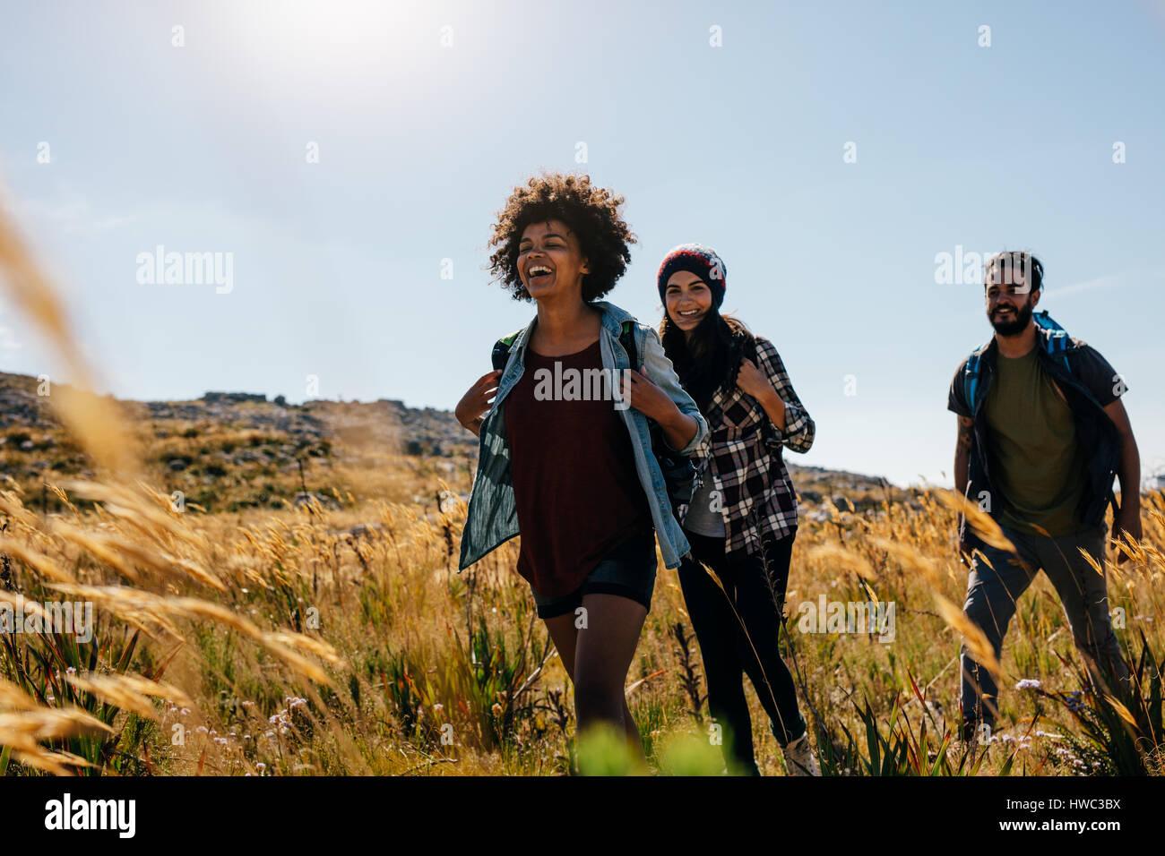 Grupo de Amigos de paseo por la campiña juntos. Feliz de hombres y mujeres jóvenes senderismo juntos en Imagen De Stock
