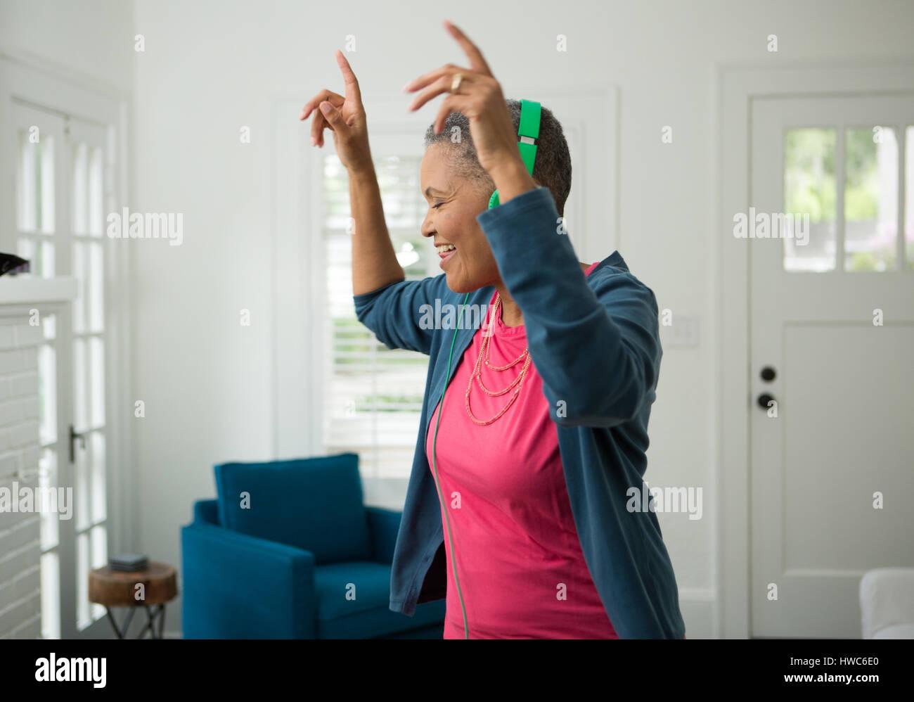 Senior mujer escuchando música con auriculares Imagen De Stock