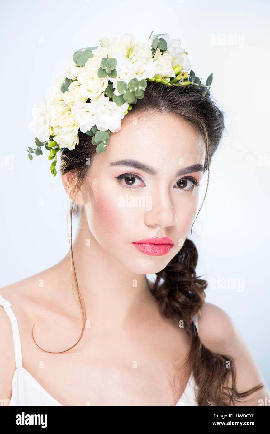 Retrato de mujer seria con flores en el cabello sobre blanco Foto de stock