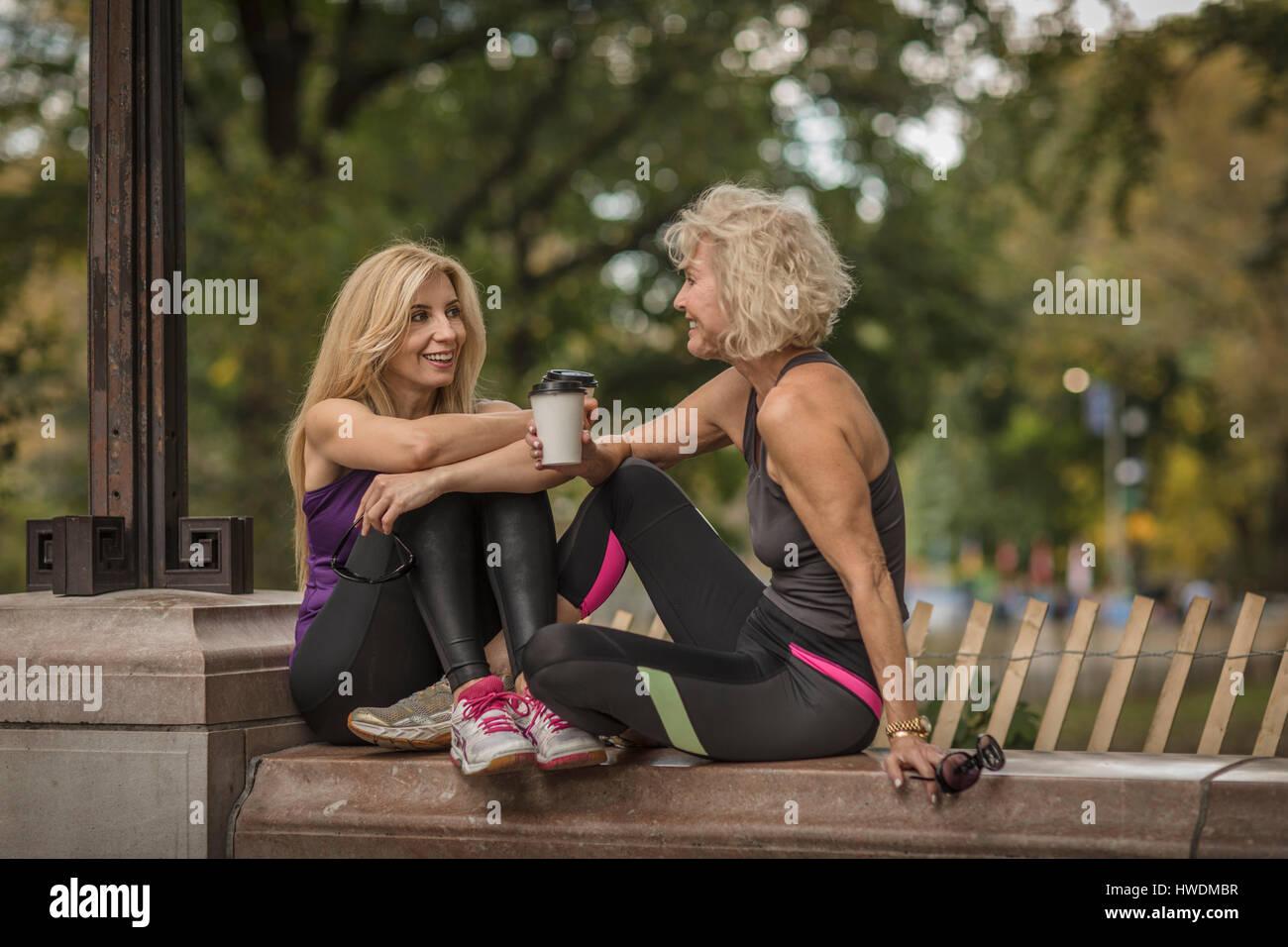 Amigas Maduras dos amigas madura formación en parque, sentados en el muro