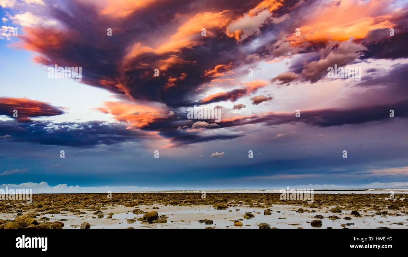 Hermosas formaciones nubosas durante el atardecer en la playa de Kina, Nueva Zelanda Foto de stock
