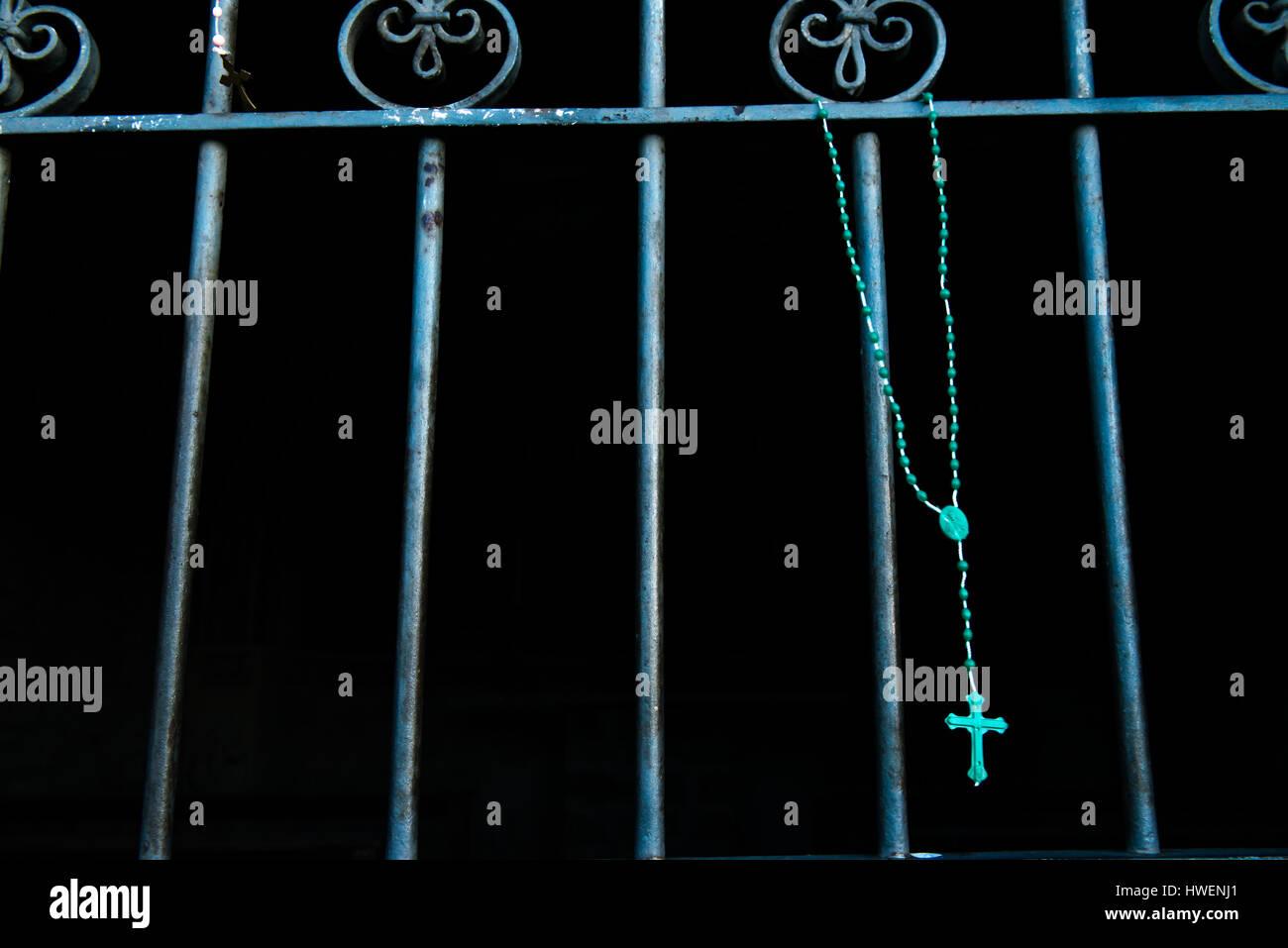 Blue rosario colgando de verjas de hierro viejo Imagen De Stock