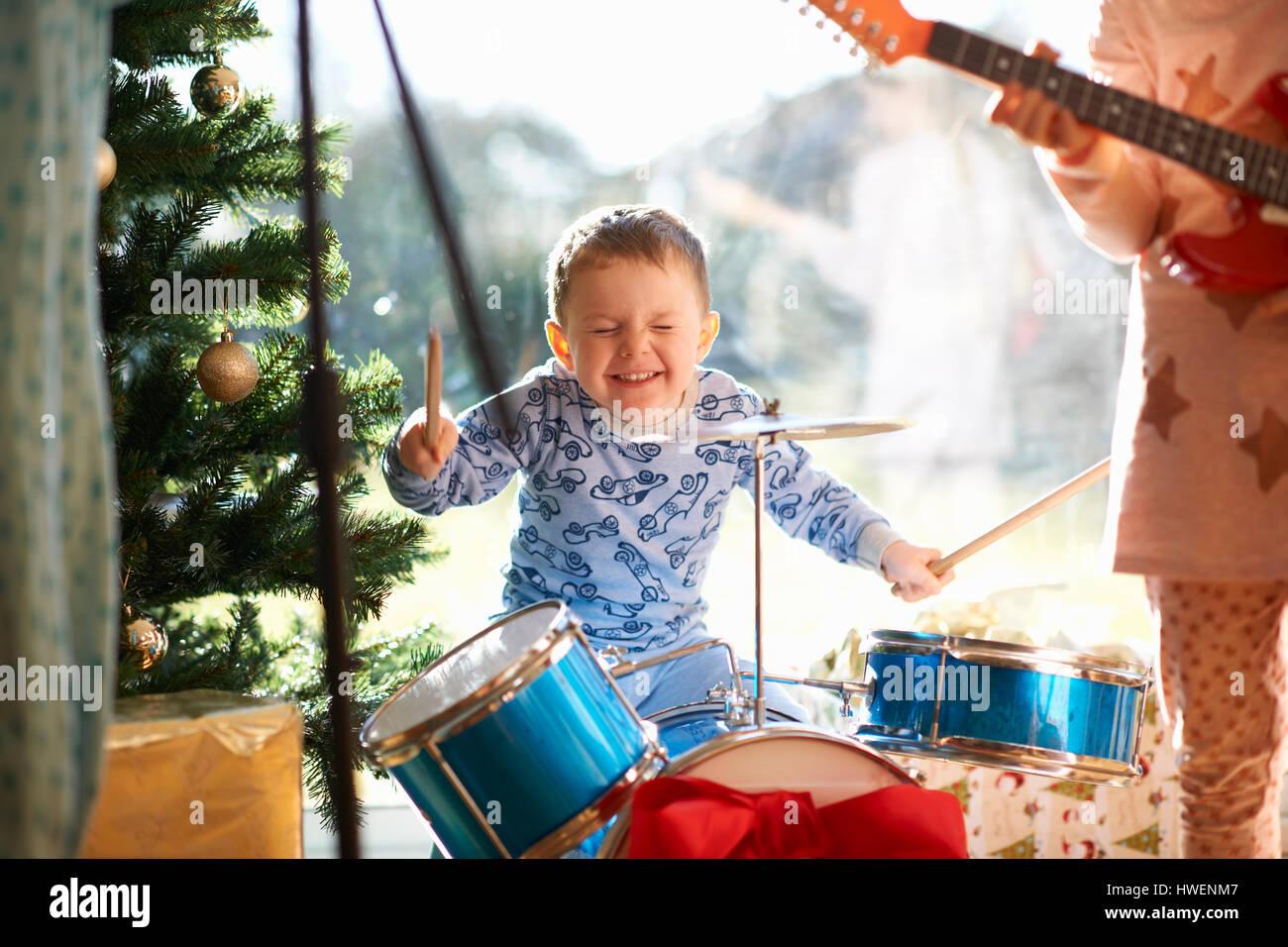 Chico y hermana jugando toy kit de batería y guitarra en el día de Navidad. Imagen De Stock
