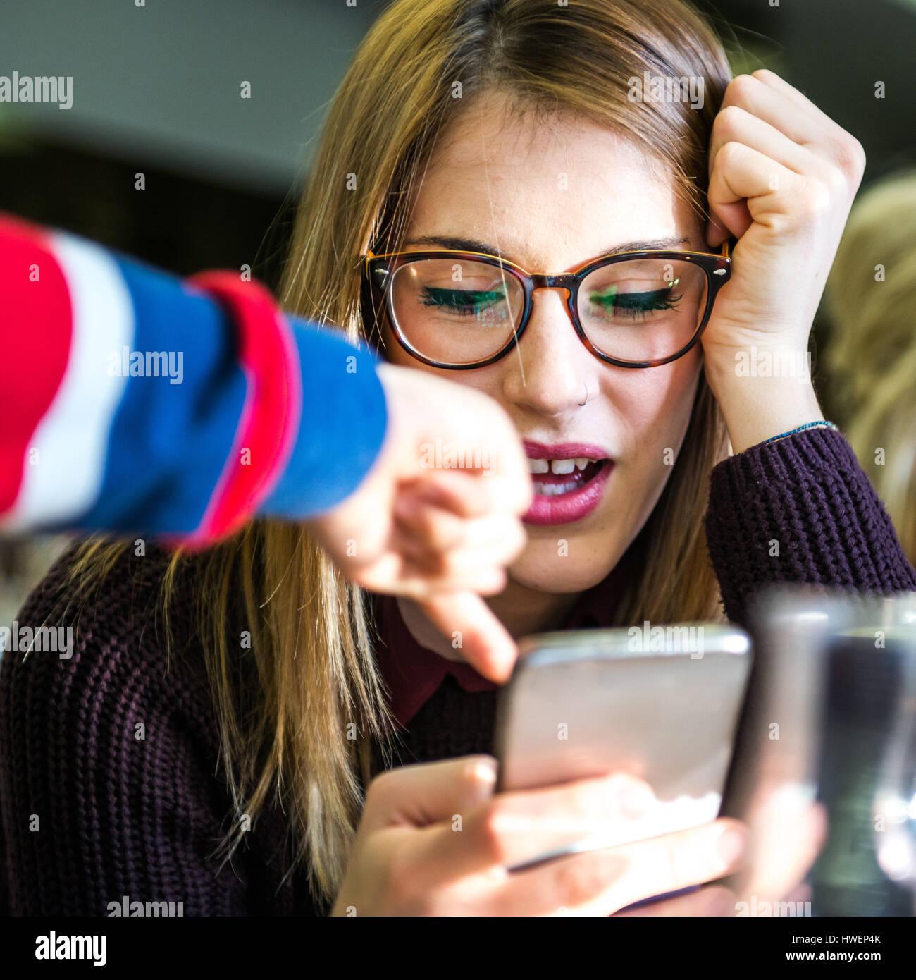 Mujer joven con chico de la mano apuntando al smartphone en cafe Imagen De Stock