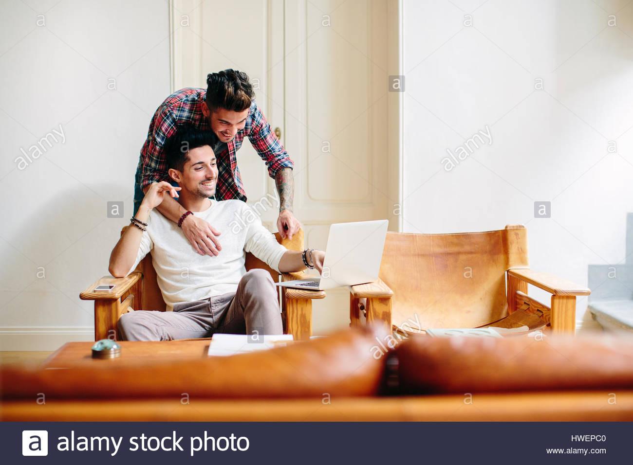 Joven de la casa, sentado en la silla, utilizando equipo portátil, su socio abrazando a él desde atrás Imagen De Stock