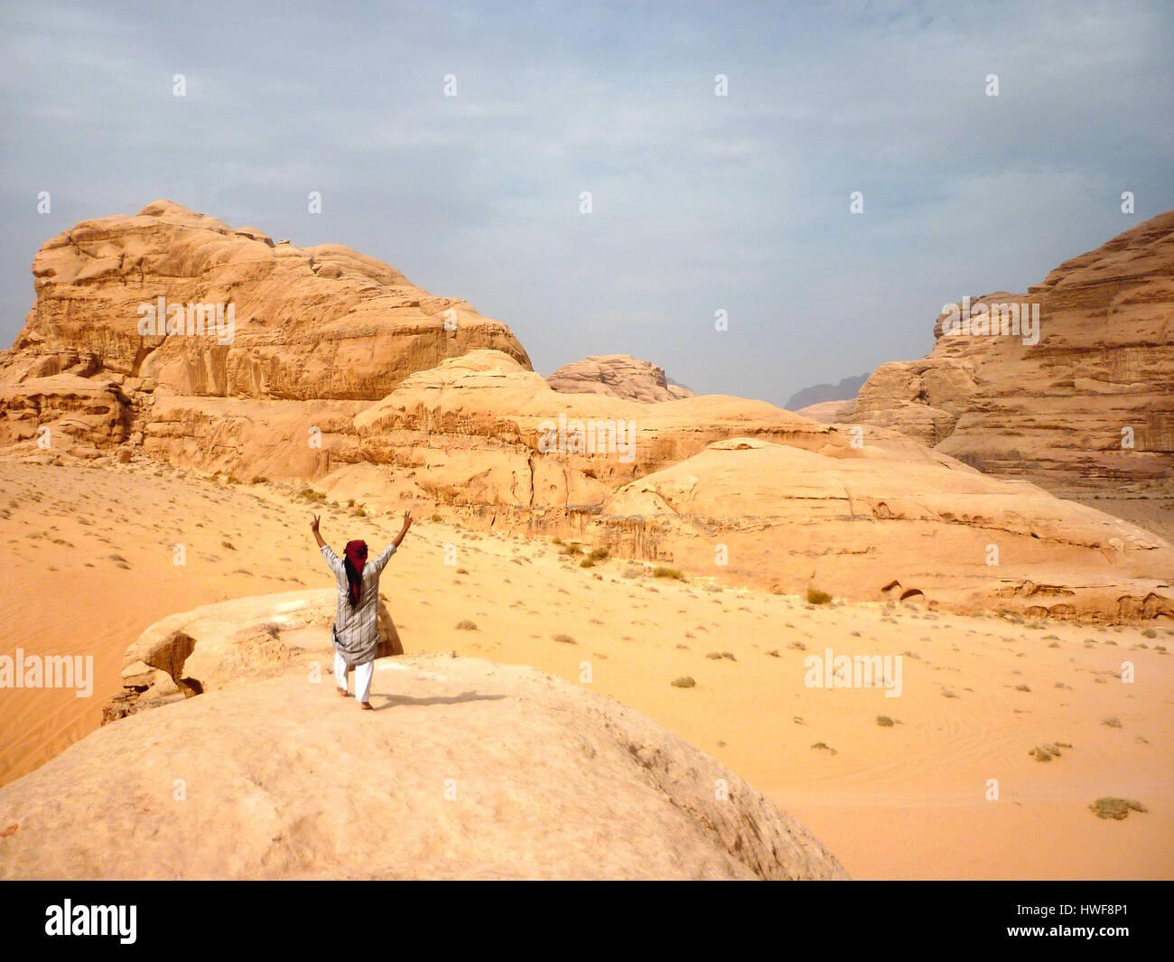 Los beduinos de pie sobre una roca en el desierto de Wadi Rum en Jordania Foto de stock