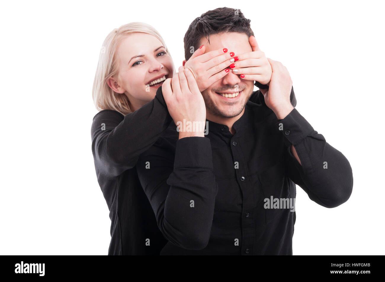 Feliz joven sorprende a su novio de la espalda aislado sobre fondo blanco. Imagen De Stock