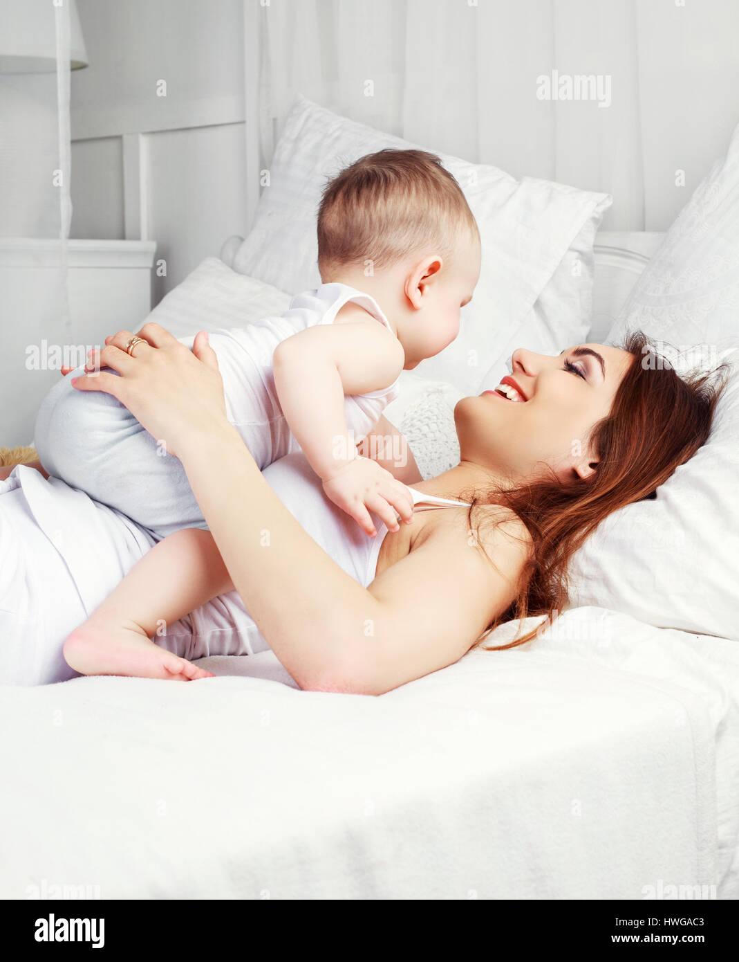 Feliz hermosa madre con su hijo de un año y medio en la cama en casa Imagen De Stock