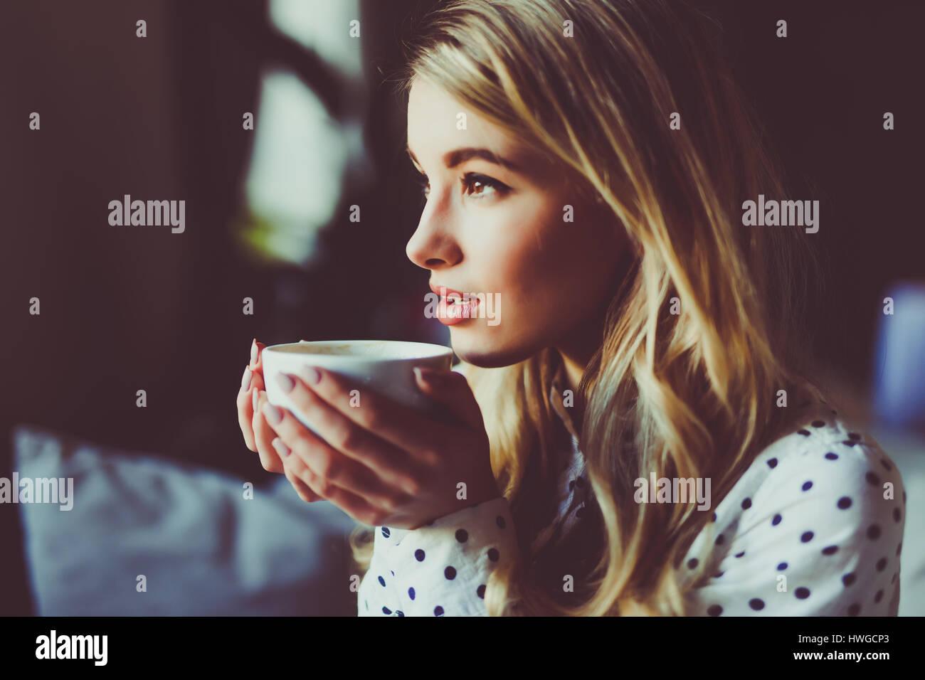 Retrato de joven mujer hermosa beber té y cuidadosamente mirando afuera de la ventana de la cafetería Imagen De Stock