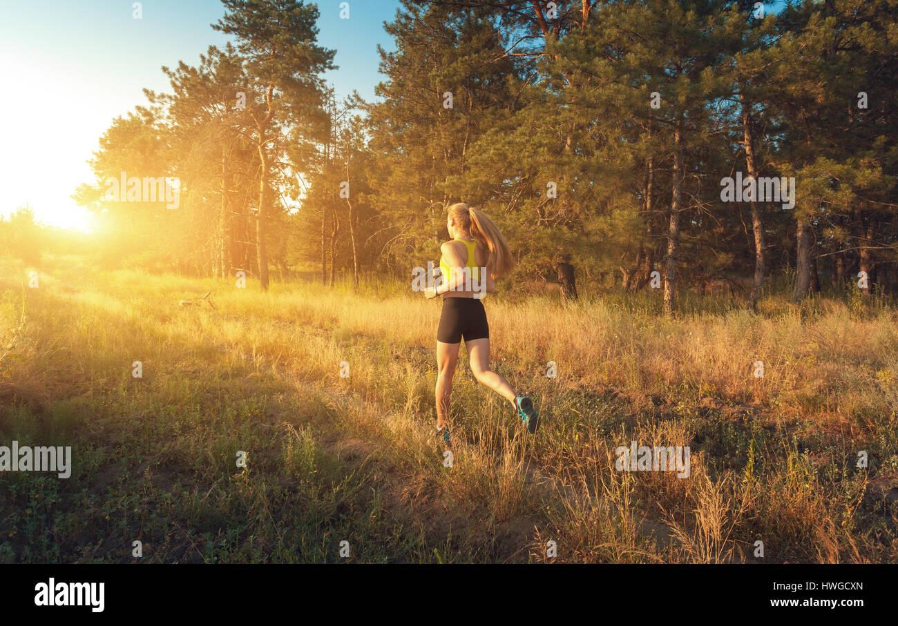 Deportivo joven niña corriendo en un campo cerca de los árboles al atardecer en verano. Atleta que se ejecuta en Foto de stock