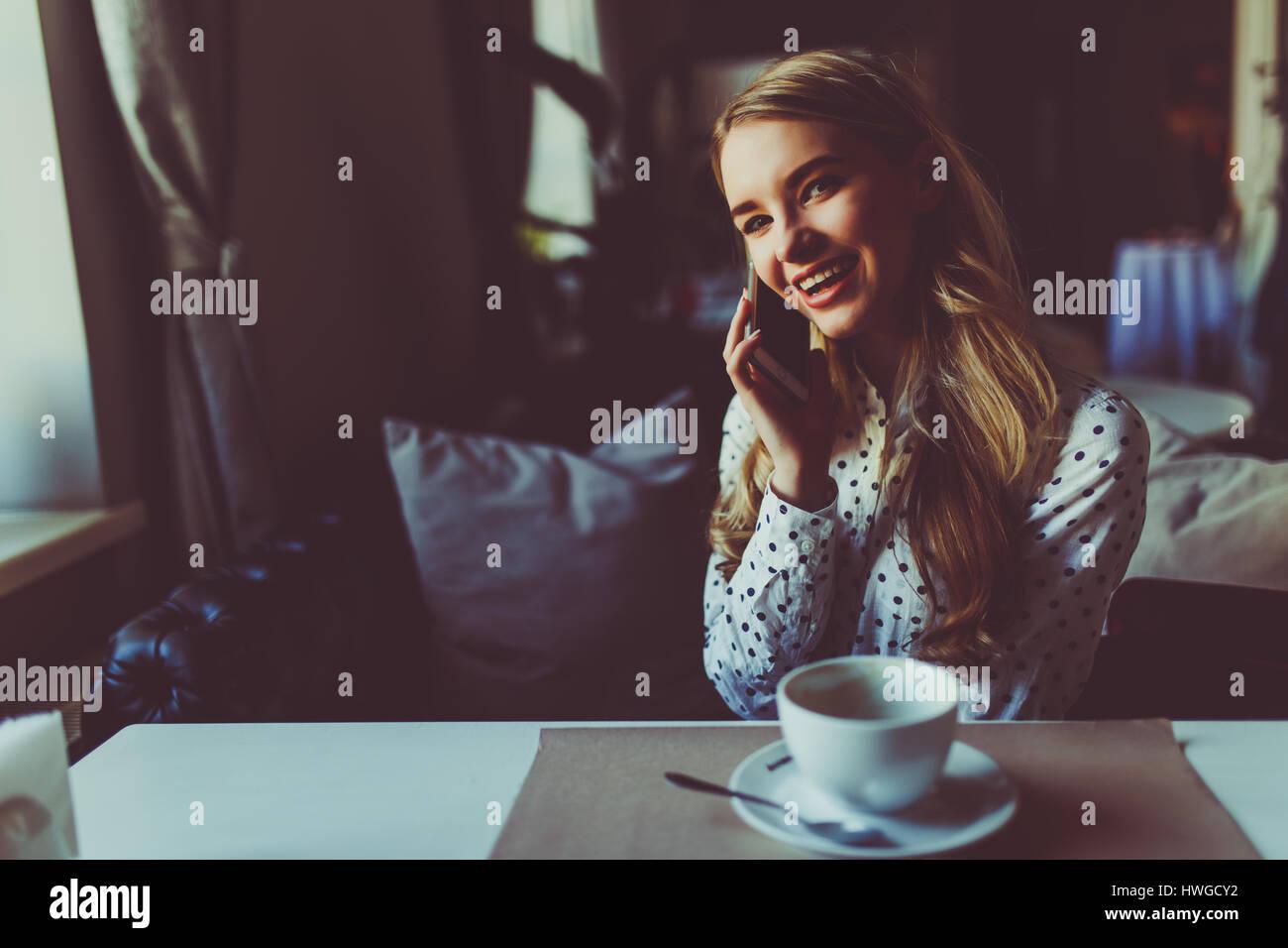 Feliz mujer hablando con teléfono celular mientras está sentado en la cafetería durante el desayuno Imagen De Stock