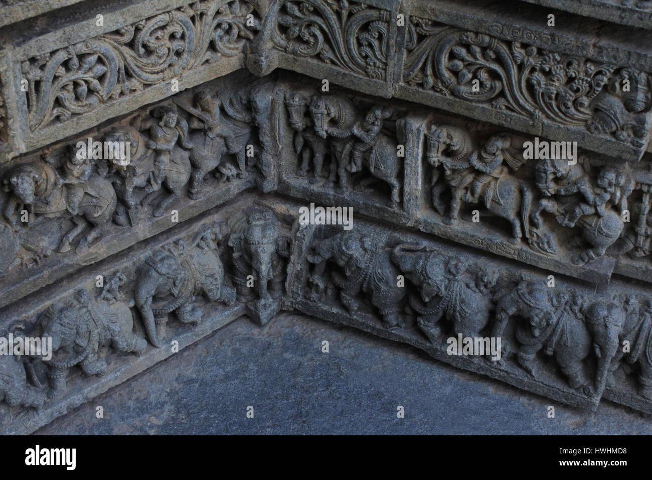 Cerca de las esculturas de piedra de follaje, guerreros, jinetes, elefantes procesión donde dos paredes de esquina satisfacer mutuamente en el santuario en la pared Chennakesa Foto de stock