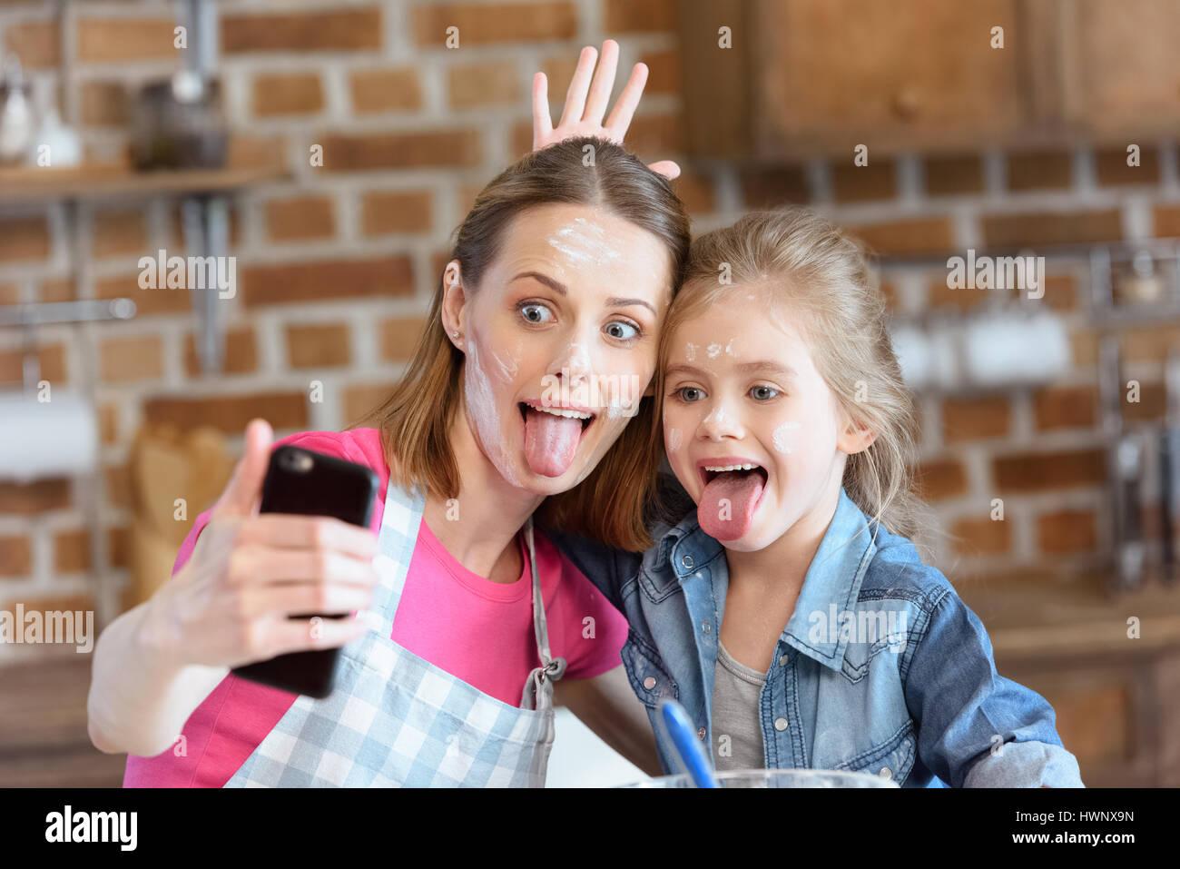Retrato de la mueca, madre e hija haciendo selfie mientras cocina en casa Imagen De Stock