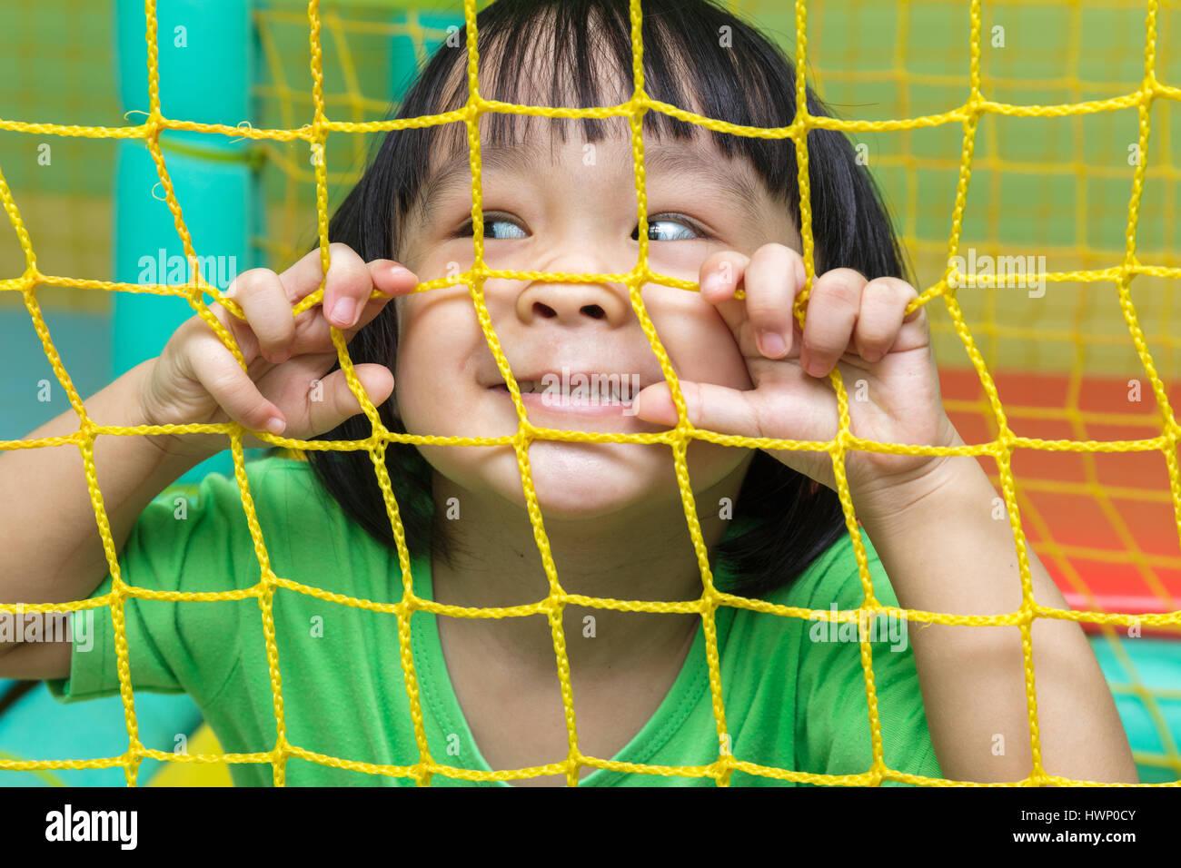 Feliz chino Asia niña jugando detrás de la red en el patio interior. Imagen De Stock