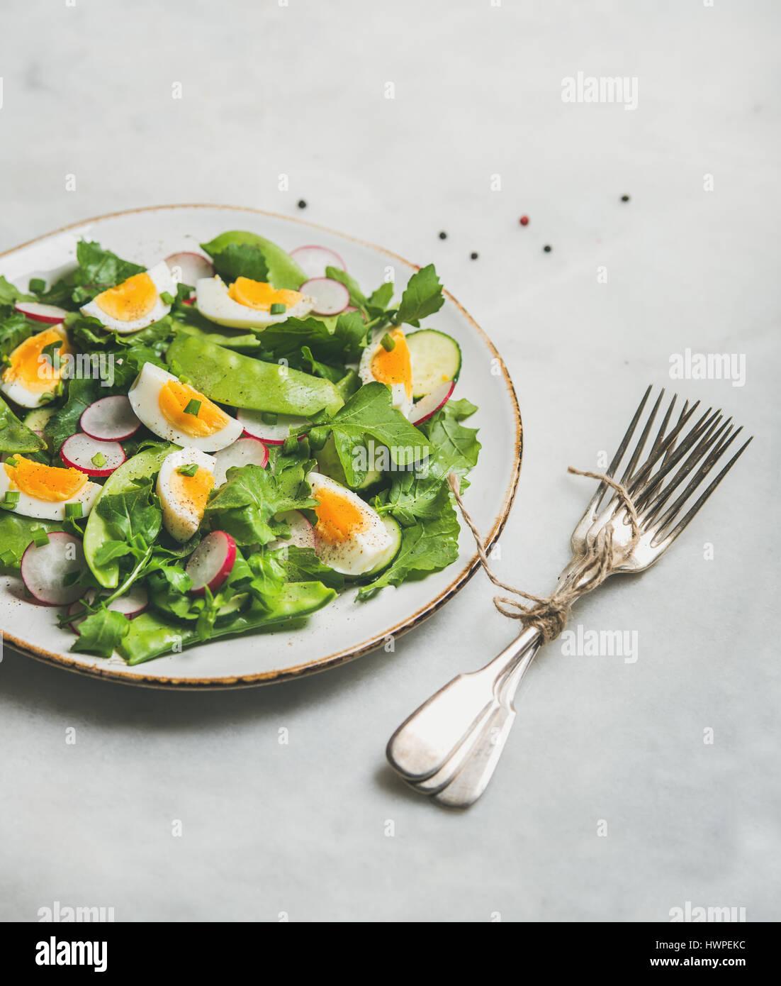 Saludable ensalada verde primavera con verduras, guisantes y huevo Imagen De Stock