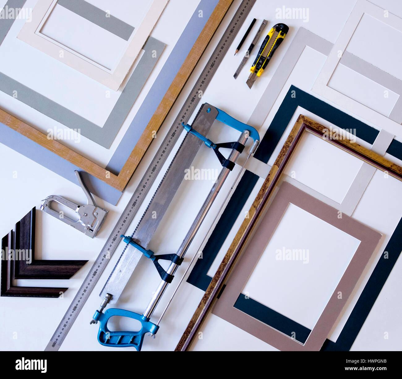 Vista aérea de los marcos de imagen con herramientas de trabajo sobre la mesa en el taller Foto de stock