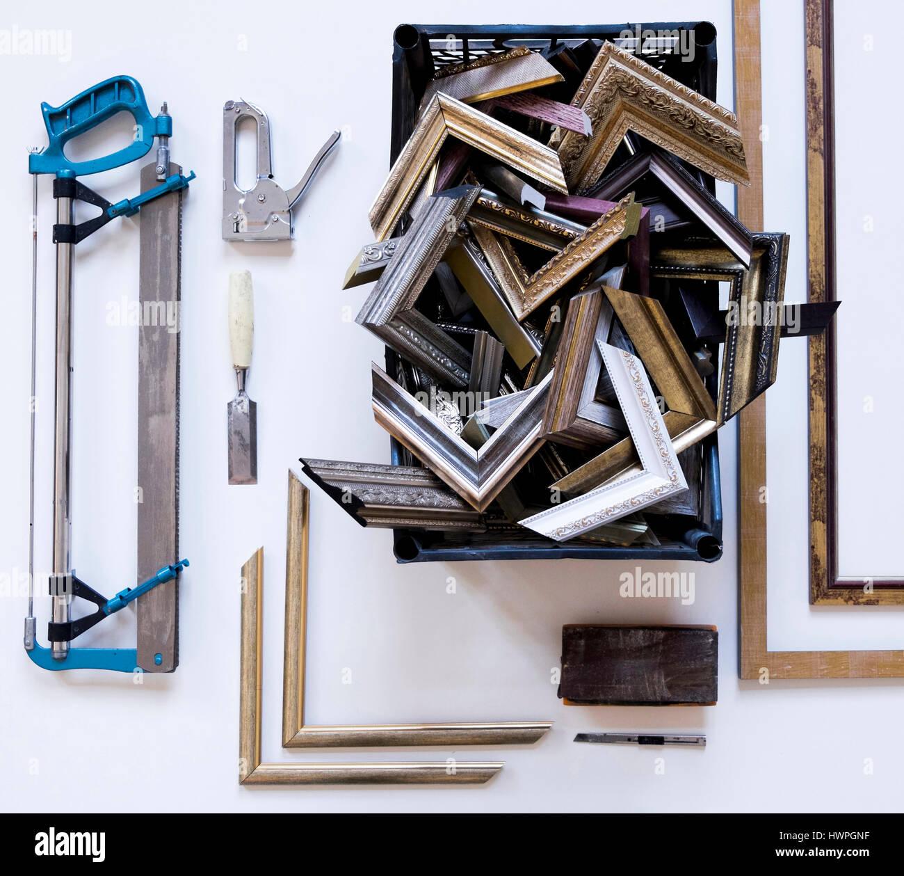 Vista aérea de los marcos de imagen y rincones con herramientas de trabajo sobre la mesa en el taller Foto de stock
