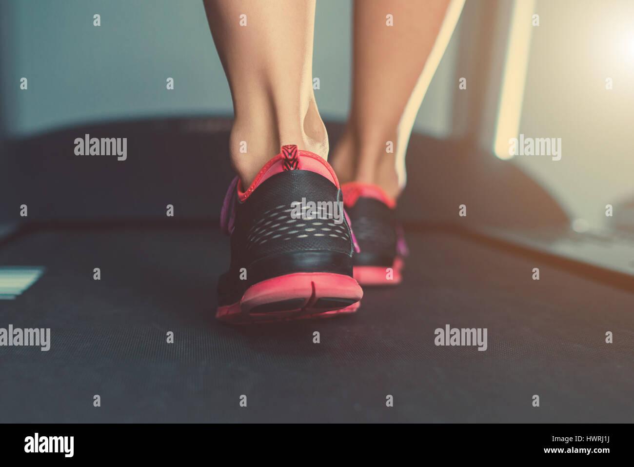 Hembra pies muscular en zapatillas corriendo en la cinta en el ...