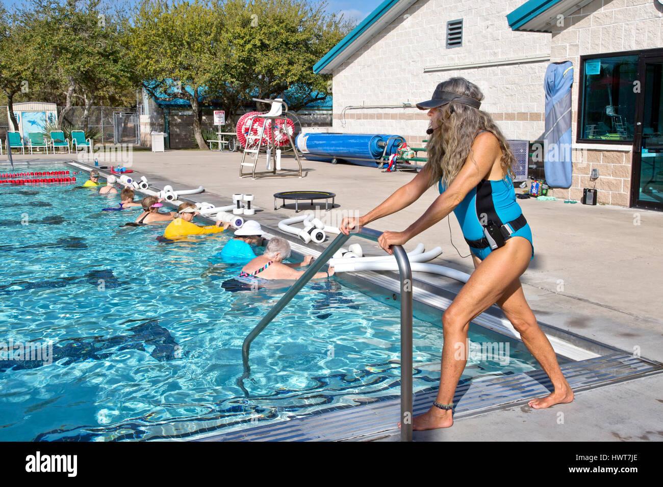 """Instructor demostrando """"elástica"""", clase de aeróbicos en el agua, un grupo de mujeres que asisten. Foto de stock"""