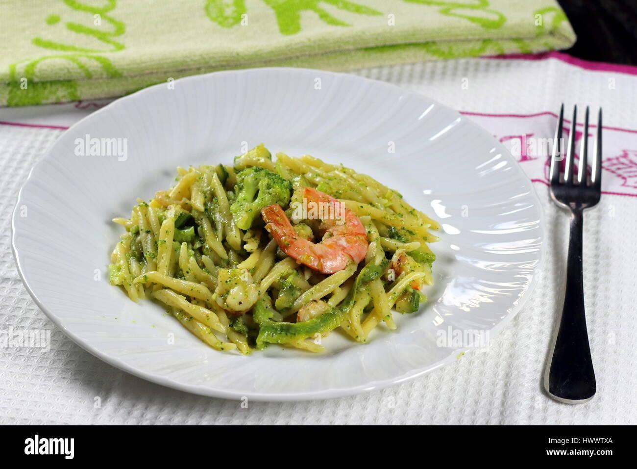 Trofie Pasta con langostinos (camarones), brócoli, zucchini (calabacín) y tomate en el manjar blanco sobre Imagen De Stock