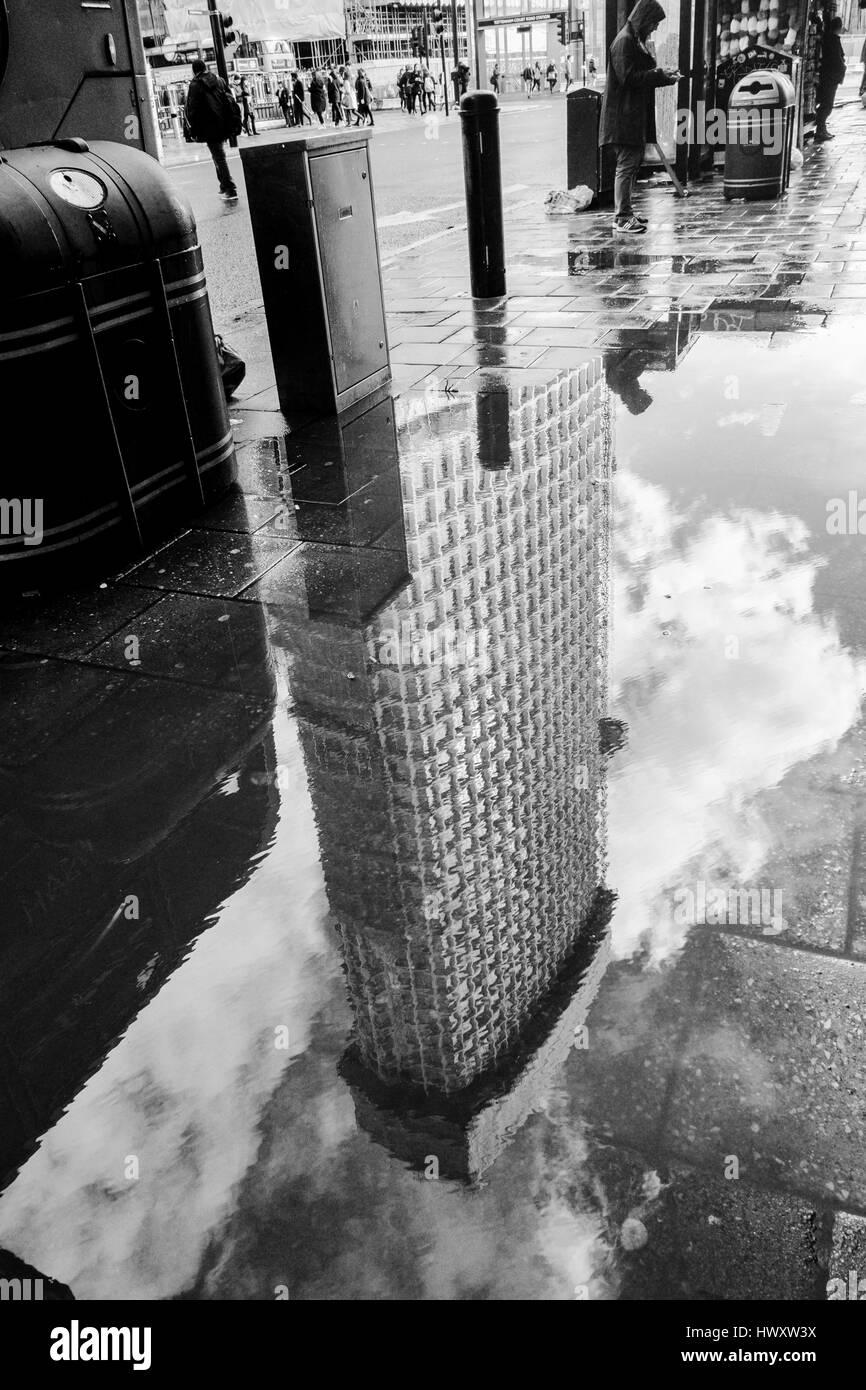 Londres en blanco y negro fotografía urbana: Punto central edificio reflejado en el charco. Londres, Reino Imagen De Stock