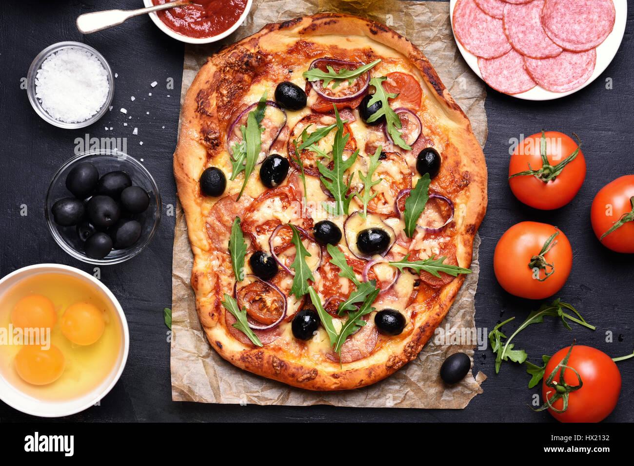 Pizza con tomate, salami y aceitunas sobre fondo negro, vista superior Foto de stock
