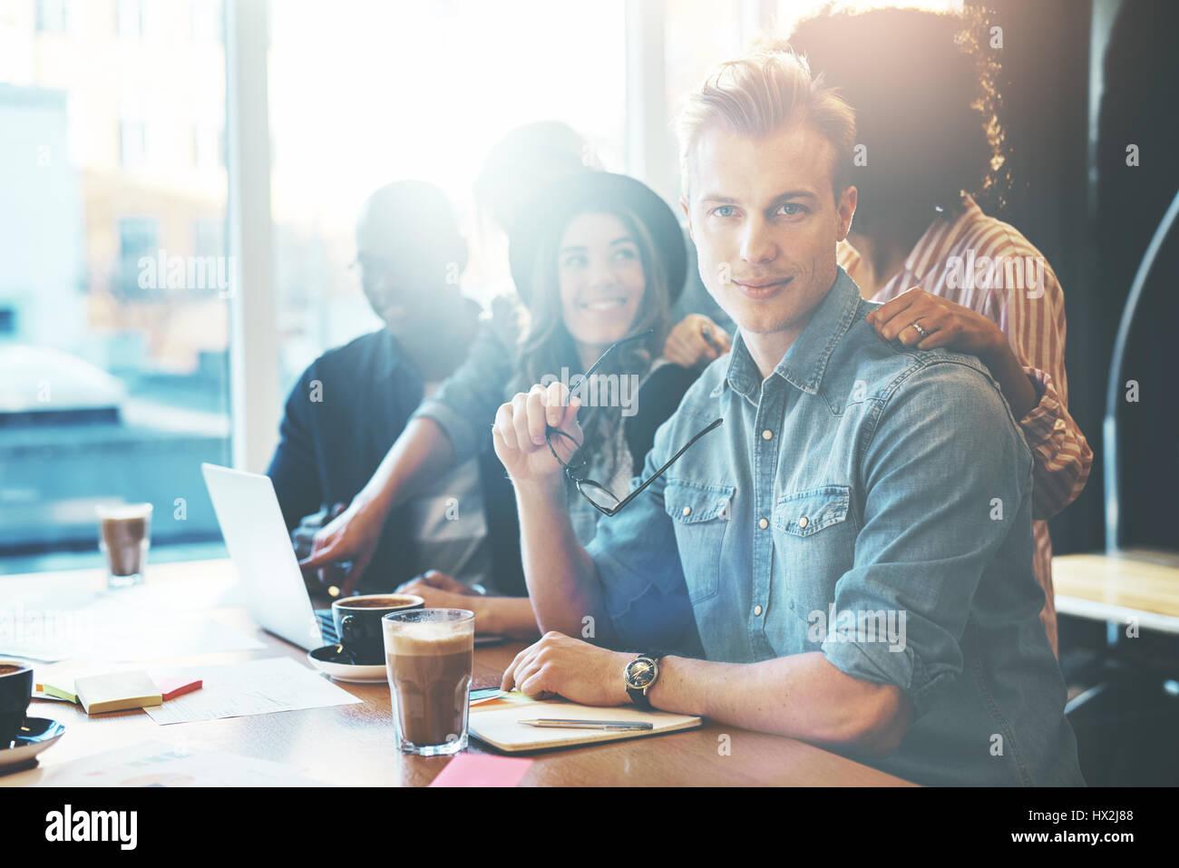 Calma empresario en ropa informal en la oficina con los compañeros de trabajo. Ventana luminosa en el fondo. Imagen De Stock