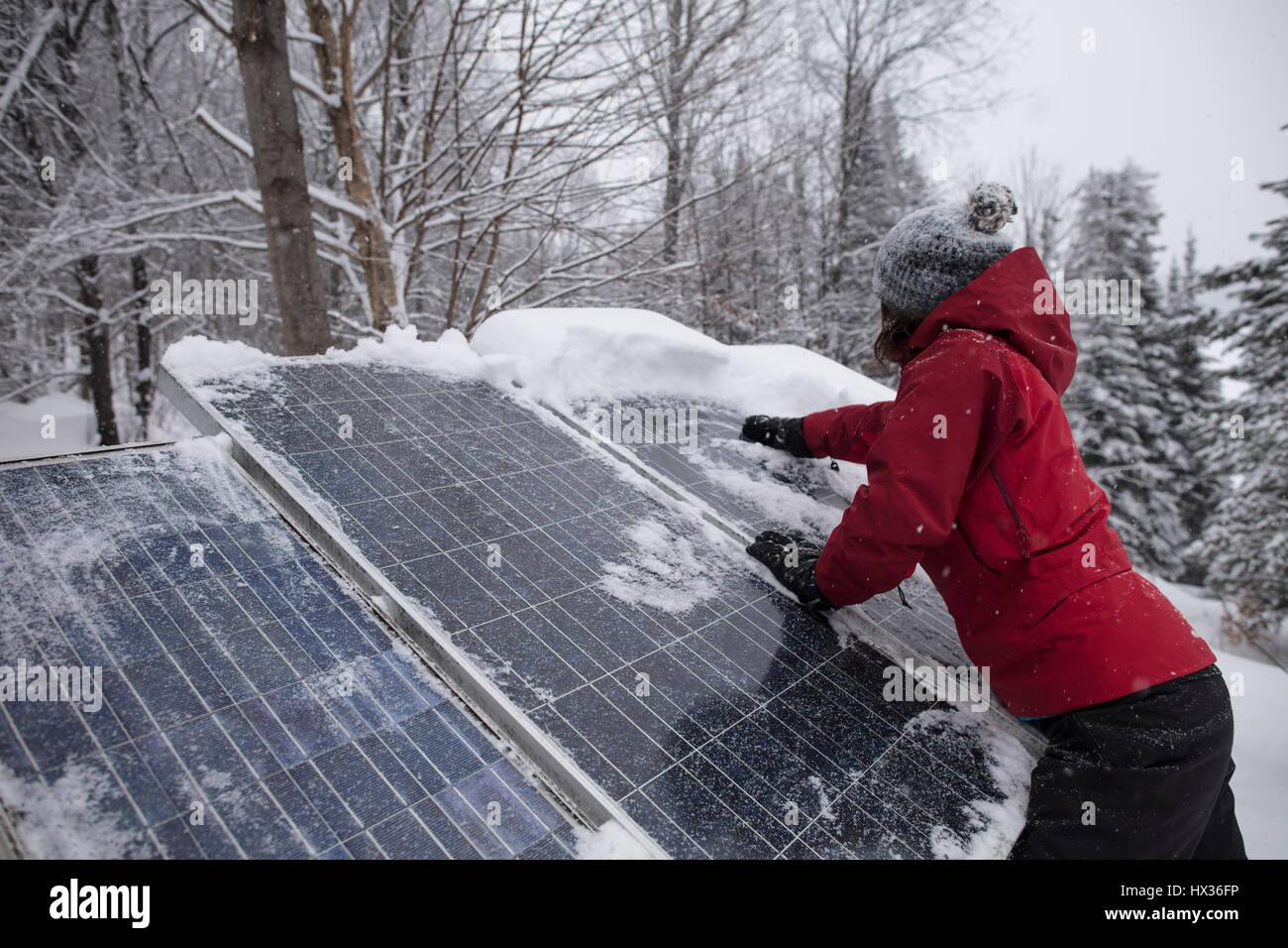 Una dama en una chaqueta roja borra la nieve de los paneles solares después de una tormenta de nieve en Hastings Imagen De Stock