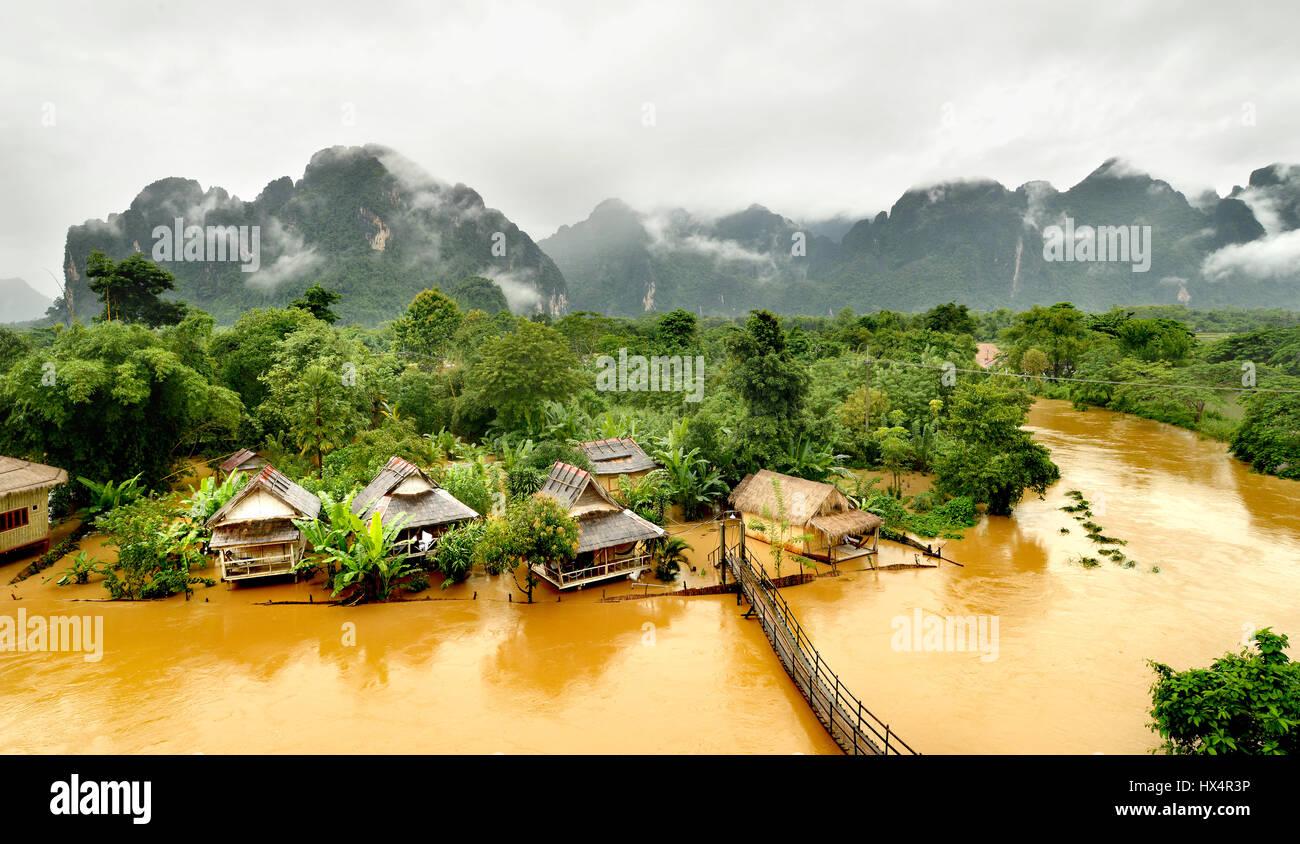 Flotando en el río lao vangvieng después de llover día en el tiempo de la mañana con la niebla en la colina Foto de stock