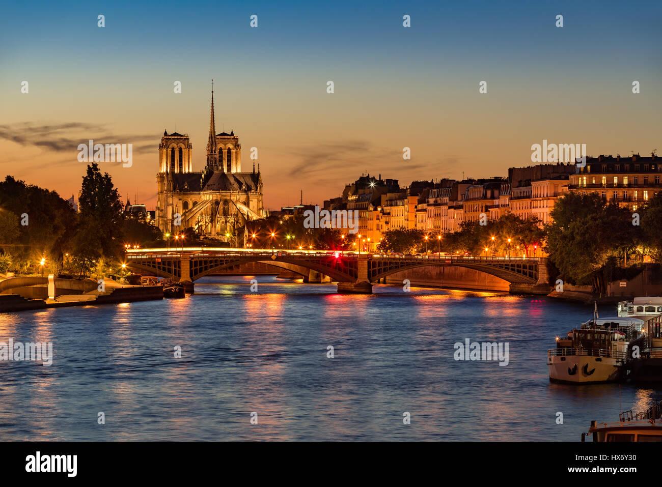 Catedral de Notre Dame, el Sena y la Ile Saint Louis en penumbra. Noche de verano con el puente de Sully y las luces Imagen De Stock