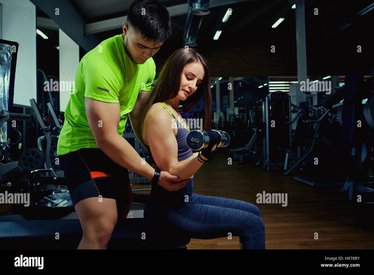 Entrenador personal ayuda a una niña, el levantamiento de pesas en el gimnasio. Imagen De Stock