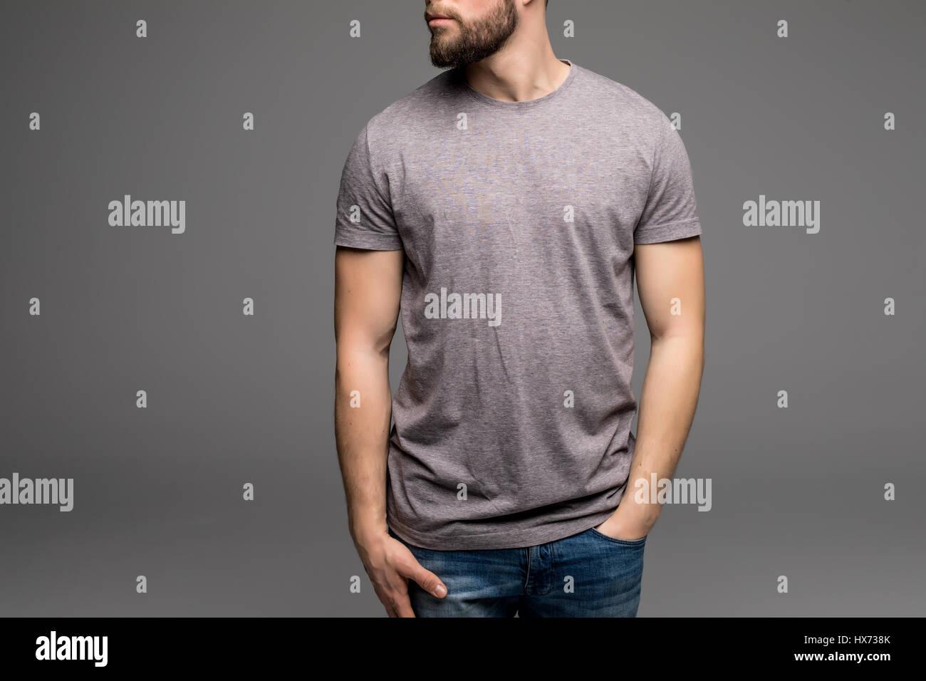 Un hombre en una camiseta gris y denims mantiene sus manos en los  bolsillos. Aislado 6642b2aaa891d