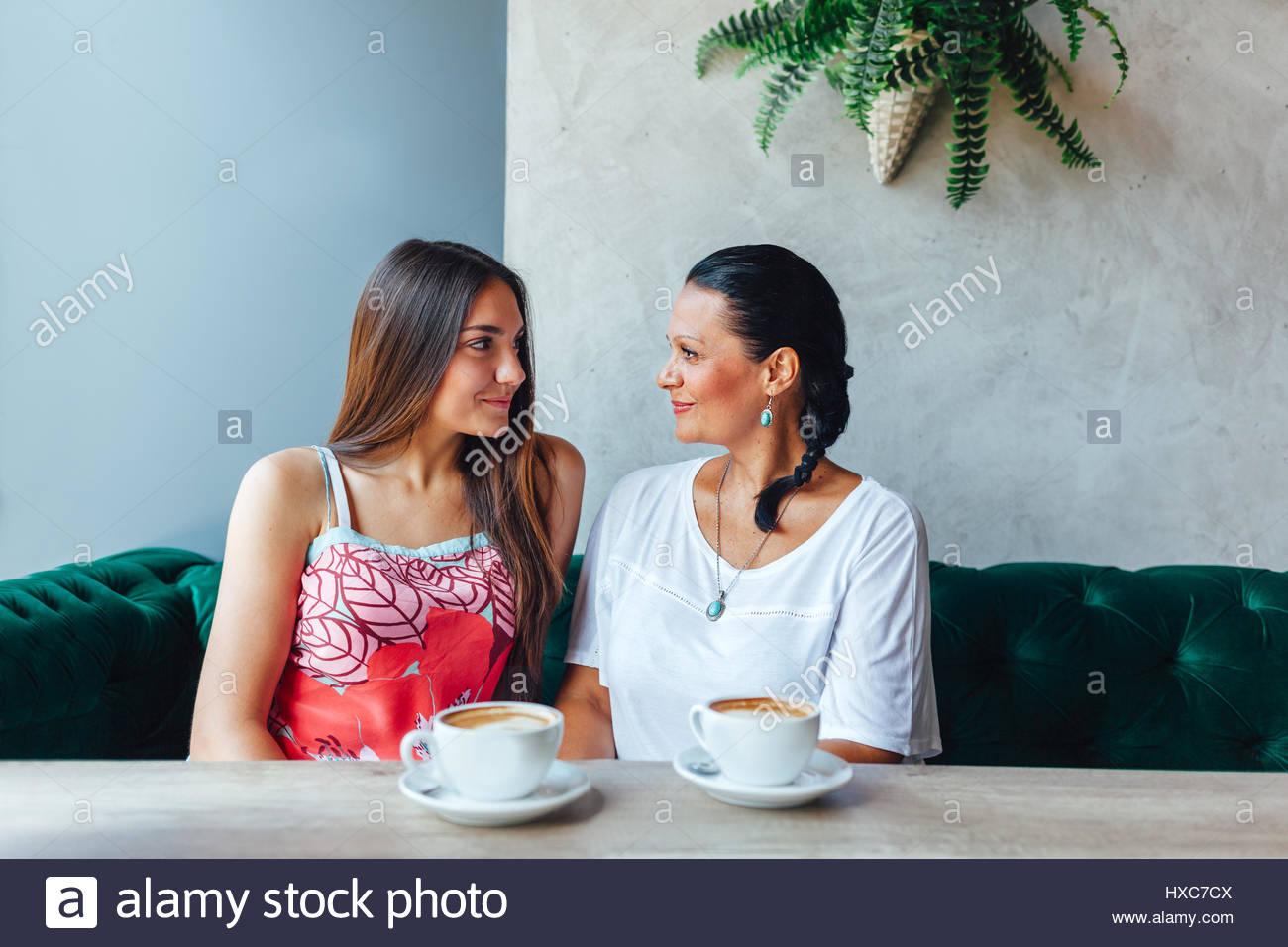 Feliz Dos mujeres hablando en la cafetería. Entre mujer y a su hija adulta bebiendo café en el café. Imagen De Stock
