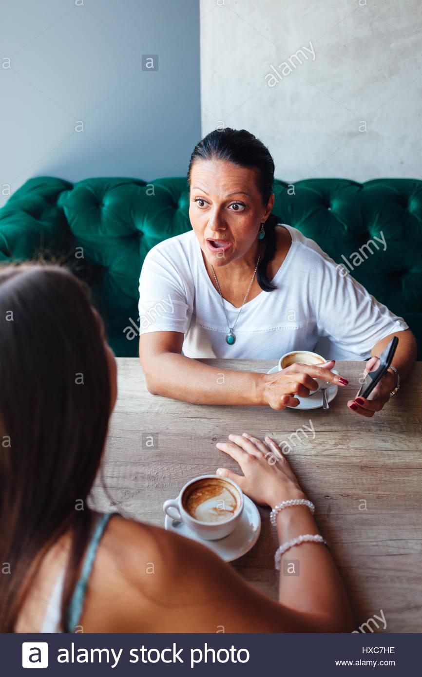 Sorprende la madre mostrando su hija algo en un teléfono móvil en un café Imagen De Stock