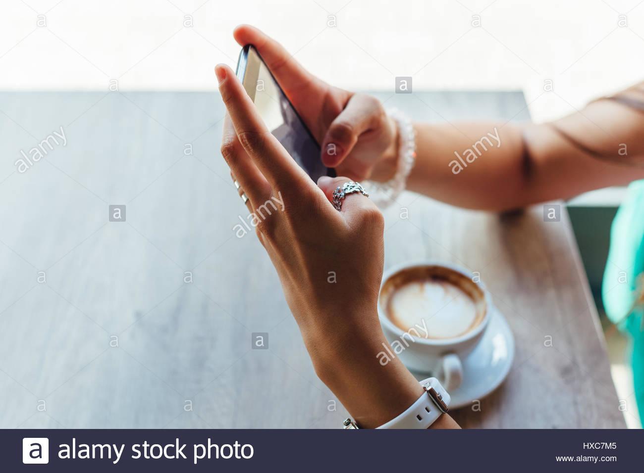 Primer plano de una mujer que utiliza un teléfono móvil en un café Imagen De Stock